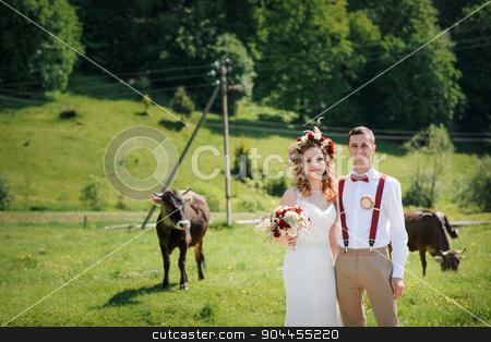 happy beautiful bride and groom walking on field in sunlight stock photo, happy beautiful bride and groom walking on field in sunlight. by timonko