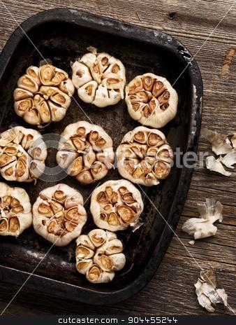 rustic roasted garlic stock photo, close up of rustic roasted garlic by zkruger