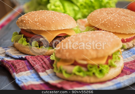 home made burgers stock photo, Closeup of home made burgers on wooden table by olinchuk