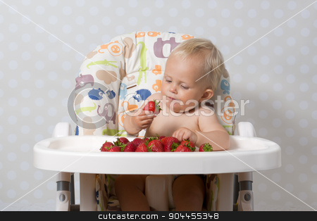 Baby girl eating strawberries stock photo, baby girl sitting in a highchair eating fresh strawberries by Kamila Starzycka