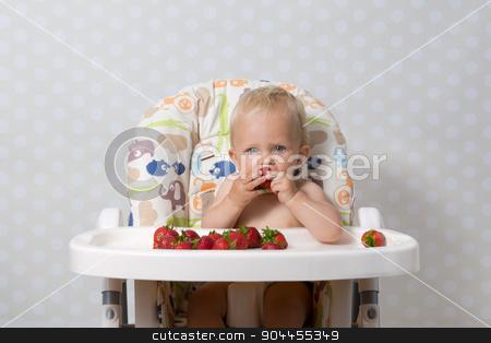 Baby girl eating strawberries stock photo, baby girl sitting in a highchair eating fresh strawberries by Kamila Starzycka