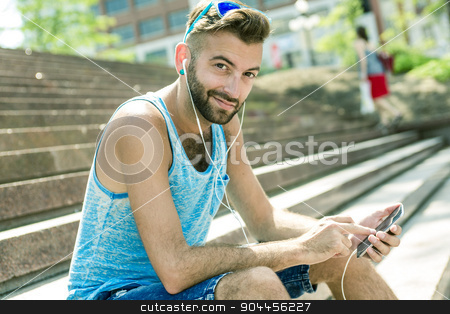 Man listening to the music with earbuds from a smart phone  stock photo, A Man listening to the music with earbuds from a smart phone  by Louis-Paul St-Onge