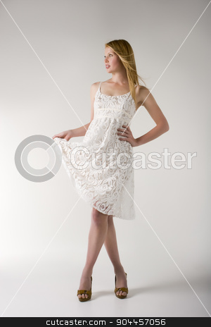Model in white dress stock photo, Model posing in a white dress and brown open toe heels in a studio by JRstock