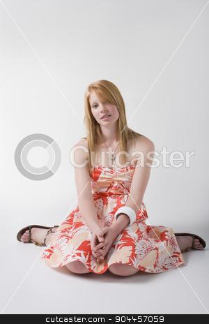 Model on orange print dress stock photo, Model sitting in a studio, wearing orange print strapless dress and sandals by JRstock