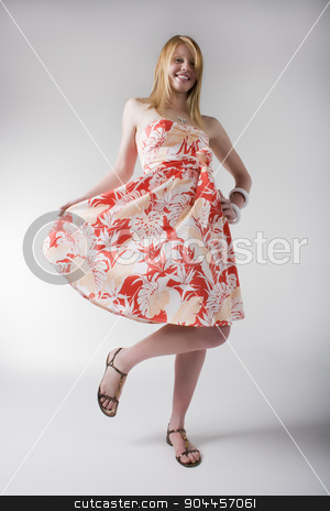 Playful woman in orange print dress stock photo, Playful woman posing in orange and white print dress and sandals by JRstock
