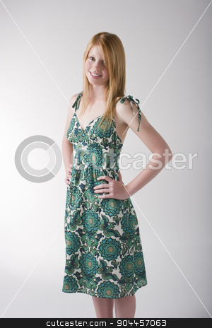 Redhead model in  green dress stock photo, Redhead model posing in a green pring dress in a studio by JRstock