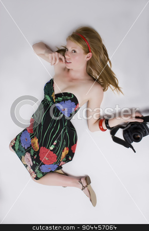 Woman in strapless dress with a camera stock photo, Woman in a strapless flower print dress laying on the ground with camera in a studio by JRstock