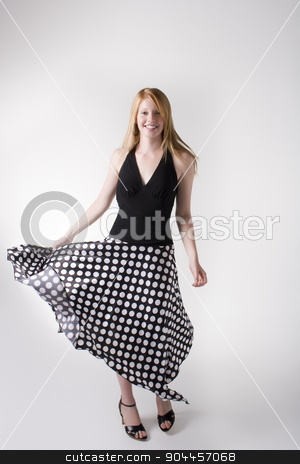 Model posing in a long skirt stock photo, Model wearing black blouse and long black skirt with white dots in a studio by JRstock