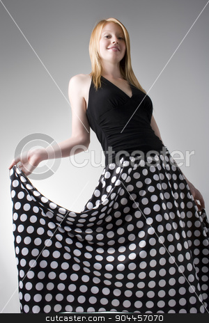 Cheerful woman in a long skirt stock photo, Cheerful woman posing in a black top and long black skirt wiht white dots by JRstock