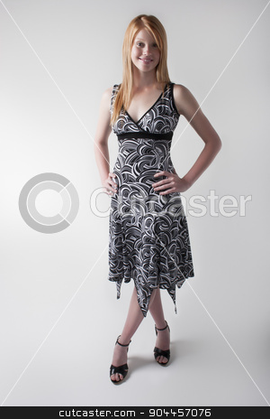 Smiling model in a black and white dress stock photo, Smiling model posing in a black and white dress and black open toe heels in a studio by JRstock