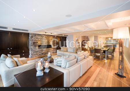 Beautiful living room with wooden floor stock photo, Beautiful living room with three sofas and a luxurious wooden floor by JRstock