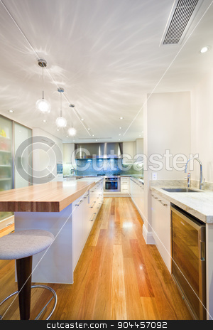 Long kitchen island stock photo, Long kitchen island, situated in the middle of a room with luxurious wooden floor by JRstock