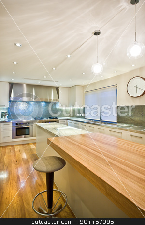 Spacious contemporary kitchen stock photo, Spacious contemporary kitchen with a beuatiful clock hanging on a wall, a big kitchen island and a wooden table by JRstock