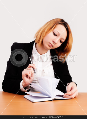Young red-haired businesswoman stock photo, caucasian businesswoman sitting at desk in casual clothes and working with dayly log by Aikon