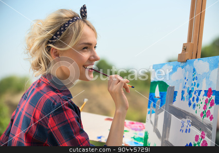 Beautiful blonde woman artist paints a colorful picture. stock photo, Beautiful blonde woman artist in a playful mood dressed in a plaid shirt. She paints a picture with a brush and paints nature by bezikus