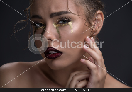 Art beauty close-up portrait of a beautiful model with curly hai stock photo, Art beauty close-up portrait of a beautiful model with curly hair. Creative make-up in the style of gold that drain tears from the eyes. by bezikus