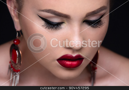 Stylish beauty close-up portrait stock photo, Stylish beauty close-up portrait. The model pouting lips dyed a rich red pamada. His ears adorn massive red earrings. Eyes closed. by bezikus