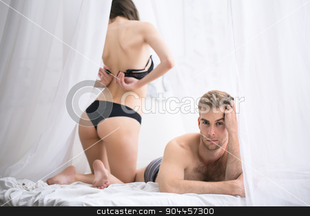 Sad morning in the bedroom of a young couple stock photo, Sad morning in the bedroom of a young couple. She undoes her bra back to the camera. Man lying on stomach propped a hand face with a sad emotion. by bezikus