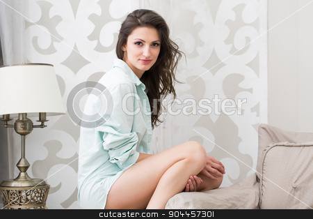 Attractive brunette in a large shirt stock photo, Attractive brunette in a large shirt sits on a chair. Against the background of a cozy interior. by bezikus