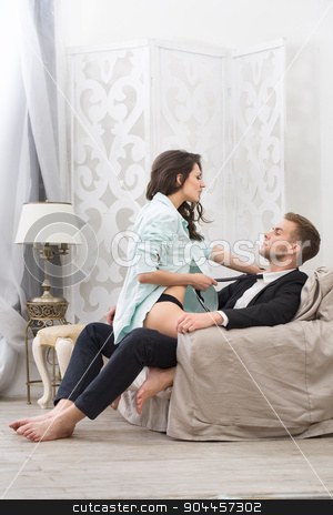 Sexy brunette seduced a guy in business suit stock photo, Sexy brunette seduced a guy in a business suit pulling him by the tie to kiss. Couple sitting in a large armchair. Photographed in a studio interior. by bezikus
