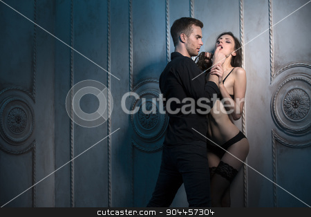 Two lovers under the wall of a beautiful interior stock photo, Two lovers under the wall of a beautiful interior. She sucks a finger partner, holding his hand by bezikus