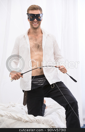 Handsome guy with whip BDSM in the leather mask stock photo, Handsome guy in the leather mask topless with unbuttoned shirt and jeans playfully holding a whip BDSM. The picture in the studio bedroom area. by bezikus