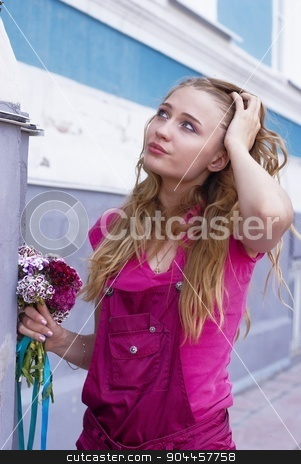 Beautiful girl with bouquet stock photo, Young attractive woman in pink with bouquet on urban background by Aikon