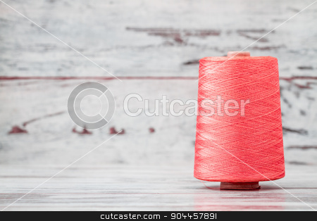 Spool of Synthetic Pink Thread on White Wooden Background stock photo, Spool of synthetic pink thread on white wooden background by OZMedia