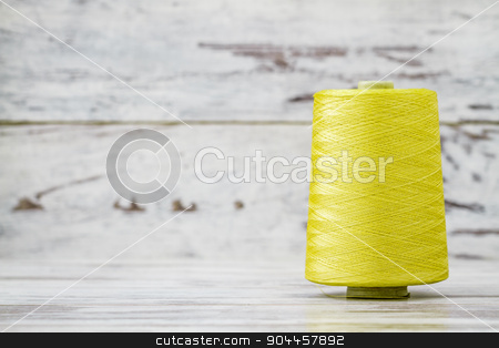 Spool of Synthetic Green Thread on White Wooden Background stock photo, Spool of synthetic green thread on white wooden background by OZMedia