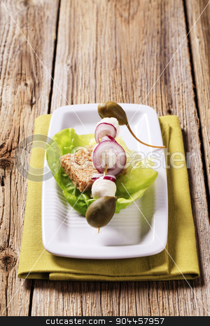 Vegetarian appetizer stock photo, Mozzarella cheese, capers and onion on a wooden skewer by Digifoodstock