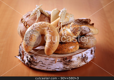 Variety of fresh bread and rolls stock photo, Variety of fresh bread on a piece of wood by Digifoodstock