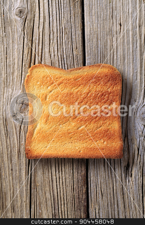 Toast stock photo, Slice of toasted bread on rough wood by Digifoodstock