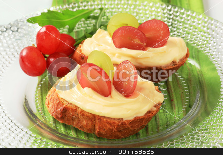 Bread and cheese spread stock photo, Slices of bread roll with cheese spread and grapes by Digifoodstock