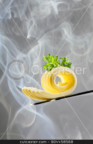 Butter curl on a knife stock photo, Butter curl on a knife in steam by Digifoodstock