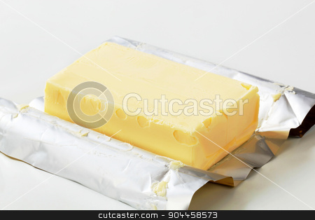 Block of fresh butter  stock photo, Block of fresh butter resting on a wrapper by Digifoodstock