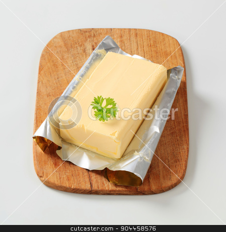 Block of fresh butter  stock photo, Block of fresh butter on a cutting board by Digifoodstock