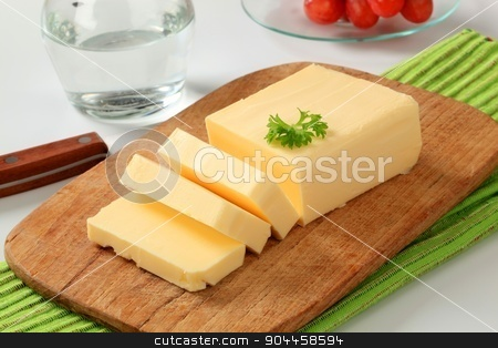 Fresh butter  stock photo, Block of fresh butter  on a cutting board by Digifoodstock