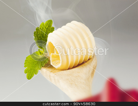 Butter curl on a wooden spoon stock photo, Butter curl on a wooden spoon in steam  by Digifoodstock