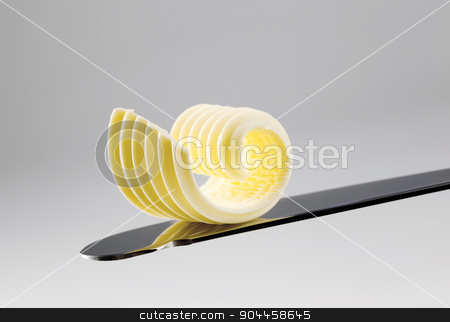 Butter curl on a knife stock photo, Closeup of a butter curl on a knife  by Digifoodstock