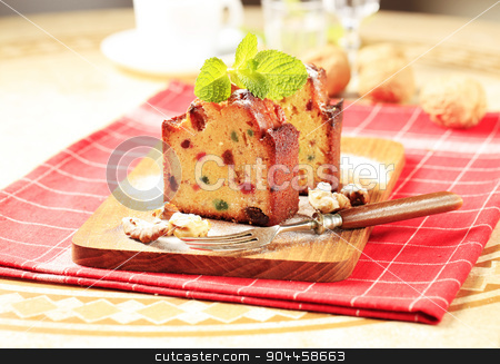 Slices of fruitcake stock photo, Two pieces of fruit cake on cutting board by Digifoodstock
