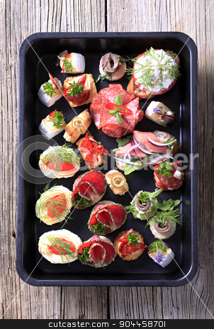 Hors d'oeuvre stock photo, Assortment of hors d'oeuvre on a black tray by Digifoodstock