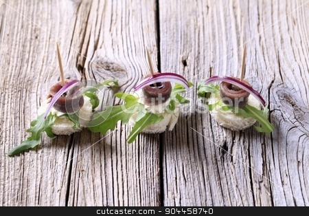 Anchovy canapes stock photo, Anchovy canapes garnished with greens and onion by Digifoodstock