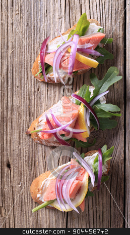 Salmon open faced sandwiches stock photo, Salmon sandwiches garnished with salad greens and onion by Digifoodstock