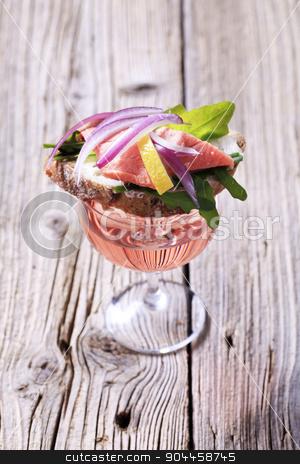 Appetizer stock photo, Salmon sandwich on a glass of rose wine by Digifoodstock