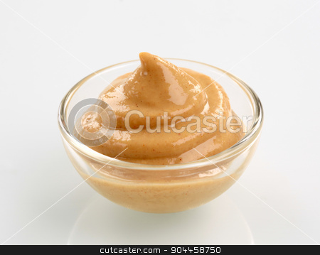 Mustard  stock photo, Swirl of spicy mustard in a small glass bowl by Digifoodstock