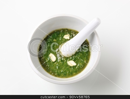 Pesto sauce in a mortar stock photo, Basil pesto with crushed cashew nuts in a mortar by Digifoodstock