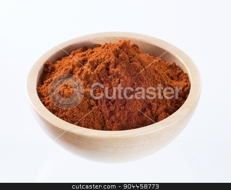 Ground red pepper  stock photo, Ground red pepper in a wooden bowl by Digifoodstock