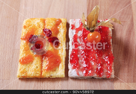Crispbread with jam and marmalade stock photo, Two slices of crispbread with strawberry and apricot preserves by Digifoodstock