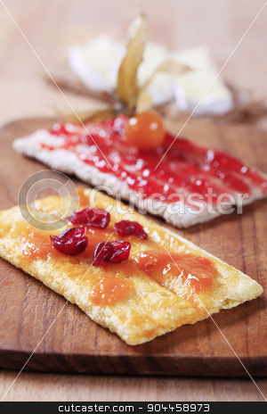 Crispbread with jam stock photo, Two slices of crispbread with strawberry and apricot preserves by Digifoodstock