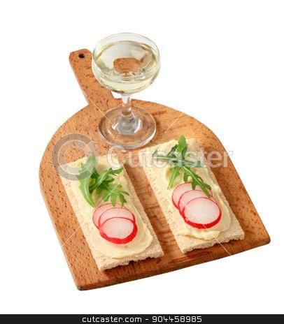 Crispbread with butter, radish and arugula stock photo, Crispbread with radish and arugula on cutting board by Digifoodstock